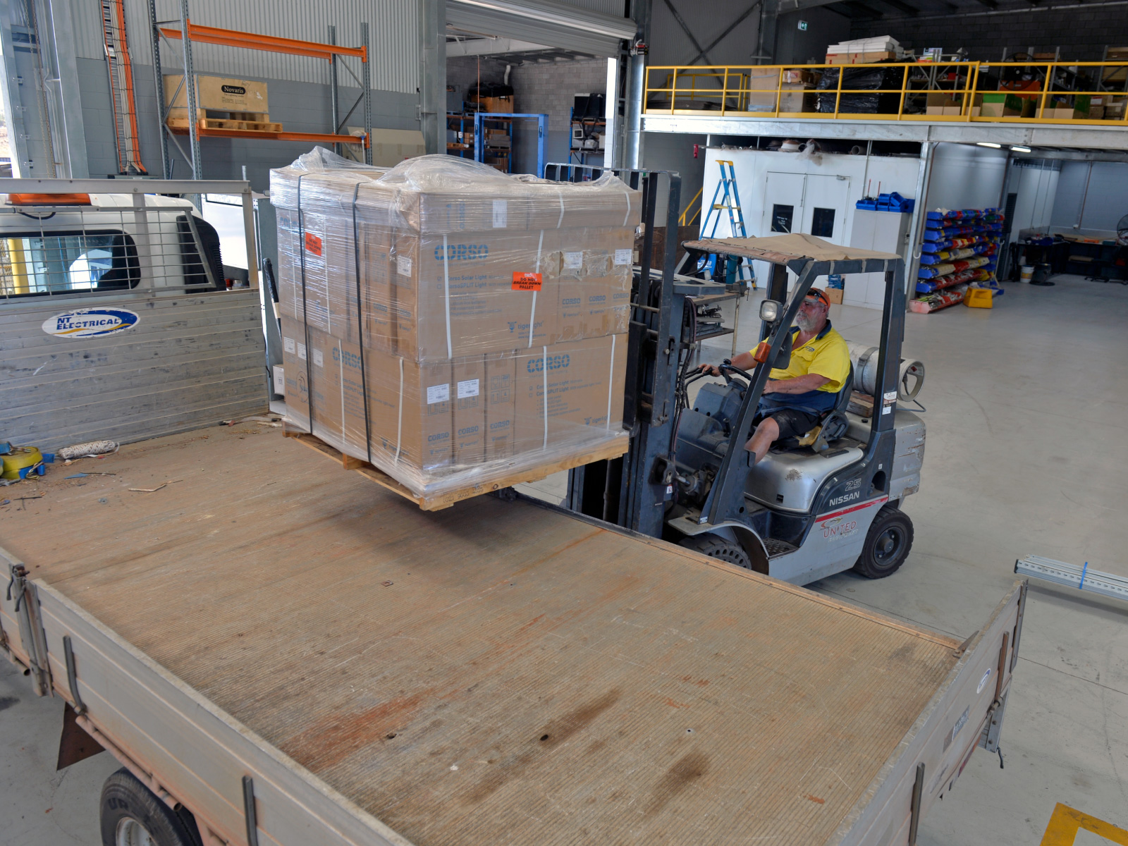 Interior facility with forklift loading electrical components onto flatbed truck.